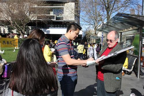 墨爾本法輪功學員馬克(Marc,右)在徵簽。(明慧網)