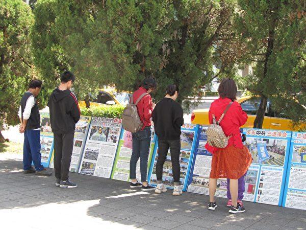 中國大陸遊客在台北故宮前的法輪功學員建立的真相點,靜靜閱讀法輪功真相展板。(明慧網)