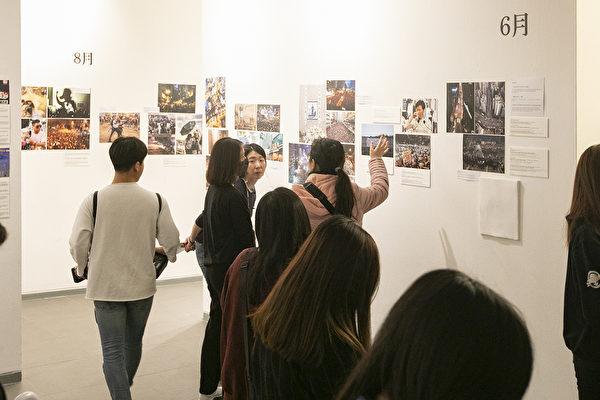 前來參觀「前因後果」照片展現場的訪客。(全景林/大紀元)