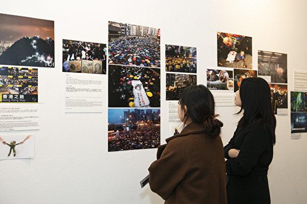 前來參加攝影展的訪客認真觀看現場照片及介紹說明。(全景林/大紀元)