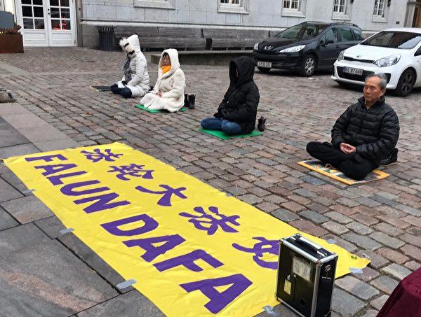 丹麥法輪大法學員在奧登賽市中心向路人介紹事件經過,呼喚正義良知。(李莎/大紀元)