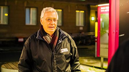 69歲的德恩(Uwe Dahn)在東柏林前秘密警察史塔西(Stasi)總部的露天展覽上,為觀眾解說柏林圍牆倒塌前,東德民眾的和平抗爭歷程。他是這段歷史的親歷者。(張清颻/大紀元)
