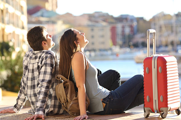 Side view of a couple of 2 tourists with a suitcase sitting relaxing and enjoying vacations in a colorful promenade. Tourism concept Fotolia