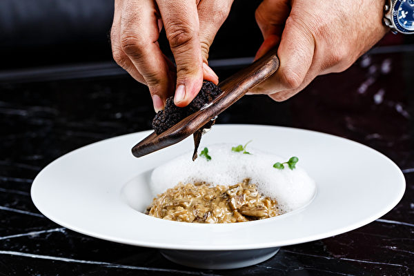risotto with truffles served in the white plate on the black background(Fotolia)