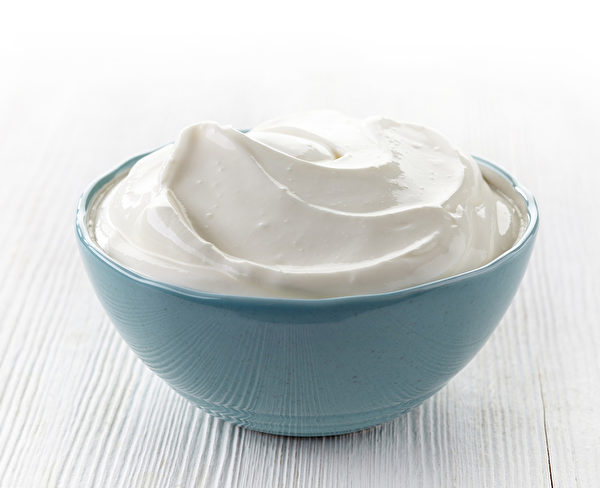 bowl of sour cream on white wooden table