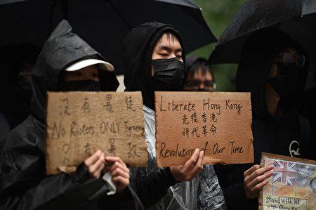 圖為香港抗議者舉牌表達訴求,「沒有暴徒、只有暴政」,「光復香港、時代革命」。(OLI SCARFF/AFP via Getty Images)