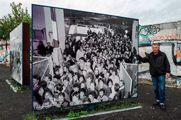 安德里亞斯.弗朗格(Andreas Falge)於1989年11月9日晚與成千上萬東柏林人一起跨過邊境,進入西柏林。圖為2019年10月1日,他在展示當年情景的圖片前留影。(JOHN MACDOUGALL/AFP via Getty Images)