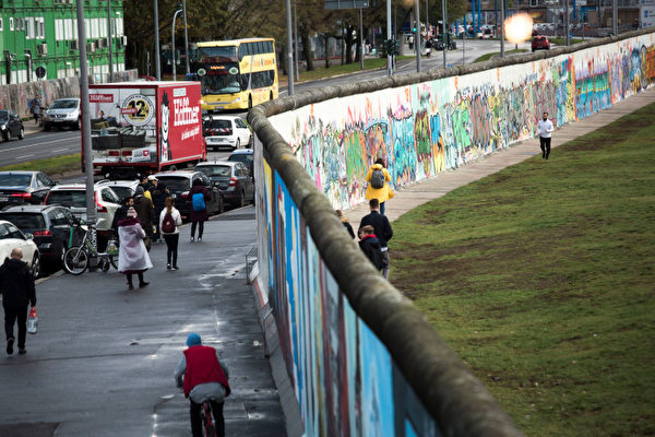 2019年11月4日,柏林政府紀念柏林牆倒塌慶祝30周年活動首日,遊客走過殘餘的柏林牆。(Carsten Koall/Getty Images)