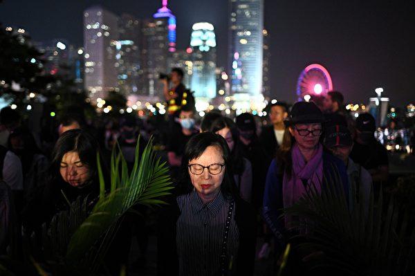 2019年11月9日,港人舉行「『主佑義士』全港祈禱及追思會」悼念周梓樂。圖為參與者默哀。(PHILIP FONG/AFP via Getty Images)