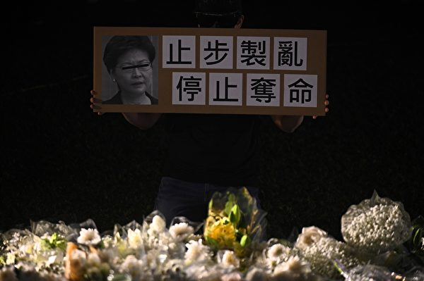 """11月9日,港人举行""""'主佑义士'全港祈祷及追思会""""悼念周梓乐。图为参与者举着要求特首林郑月娥止步制乱、停止夺命的牌子。(PHILIP FONG/AFP via Getty Images)"""
