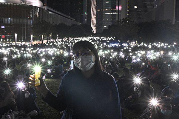 """2019年11月9日,香港民众在金钟添马公园举行""""主佑义士""""全港祈祷及追思会。民众举起手机,并打开自带灯,现场一片光海。(HILIP FONG/AFP via Getty Images)"""