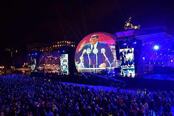 11月9日晚,十萬多觀眾參加了柏林市中心地標勃蘭登堡們前的慶祝活動,大型屏幕上打出了當年美國總統甘迺迪在西柏林演講的畫面,他的名句「我是柏林人」鼓舞著當時被柏林圍牆圍困的柏林人堅持自由民主價值。(TOBIAS SCHWARZ/AFP/Getty Images)