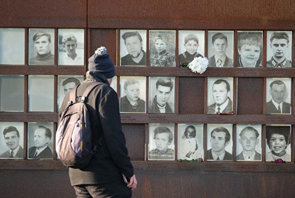 2019年10月31日,一名遊客在穿越柏林牆遇難者的相片前觀看。 (Sean Gallup/Getty Images)