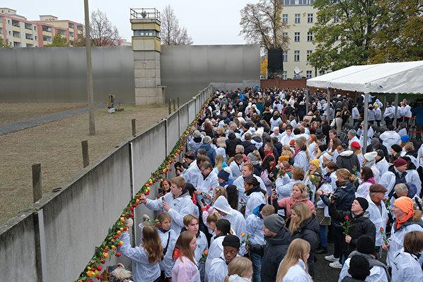 在柏林圍牆倒塌30周年紀念活動上,人們把手中黃色和橙色的玫瑰插在牆上,緬懷那些因為共產主義暴政付出生命代價的勇士們。 (Sean Gallup/Getty Images)