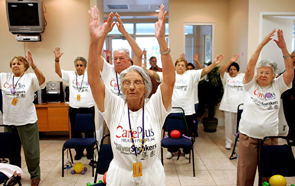 MIAMI - MARCH 22: Concepcion Cartaya (C) stretches as she listens to an exercise instructor lead their class during a work out at the CAC-Florida medical center March 22, 2007 in Miami, Florida. The center, formerly the Clinica Asociacion Cubana and now owned by Humana, provides seniors with regular primary care physicians and access to specialists several times a week. The center, emphasizing its Cuban approach, provides a place not only where health care is provided, but a kind of meeting place for the community where patients can be found playing card games, exercising, enjoying refreshments and participating in bingo tournaments and other events. (Photo by Joe Raedle/Getty Images)