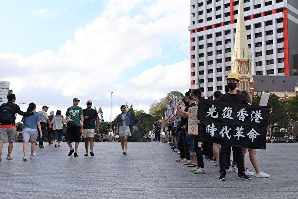 11月2日下午三點半,布市部份港人響應全球「112求援國際 堅守自治」活動,在位於市中心的中領館對面喬治國王廣場舉行了聲援集會,一些行人邊走邊讀展板(楊裔飛/大紀元)