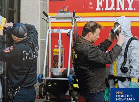 消防隊人員為醫護人員穿戴好個人防護裝備。