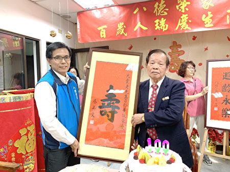八德榮家副主任鄭源敏(左)代轉蔡英文總統壽屏給百歲人瑞彭光貴。