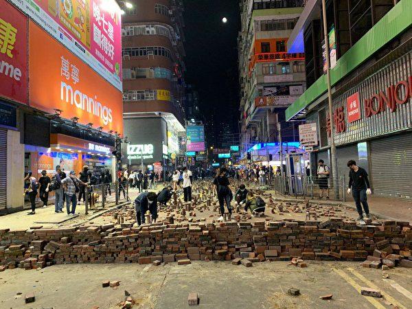 旺角白天車水馬龍,一入夜就成為城市游擊戰的戰場。抗爭者就地取材,設立磚頭陣。(宋碧龍/大紀元)