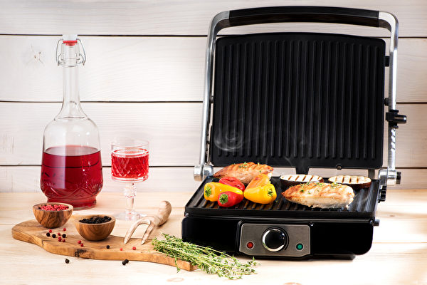 Chicken breast and vegetables on an electric indoor grill. (Shutterstock)