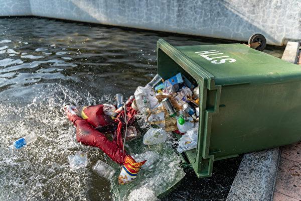 2019年9月22日,民眾把中共血旗扔進垃圾桶並推入水池。(Anthony Kwan/Getty Images)