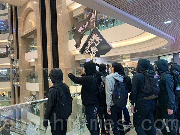 2019年12月24日平安夜,港人在各區商場發起「和你Sing,願平安歸香港」活動。圖為在銅鑼灣時代廣場喊口號。(韓納/大紀元)