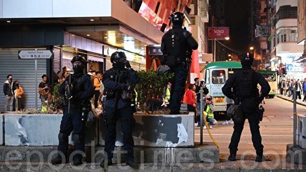 2019年12月25日晚間,在香港旺角彌敦道上速龍持槍戒備。(文瀚林/大紀元)