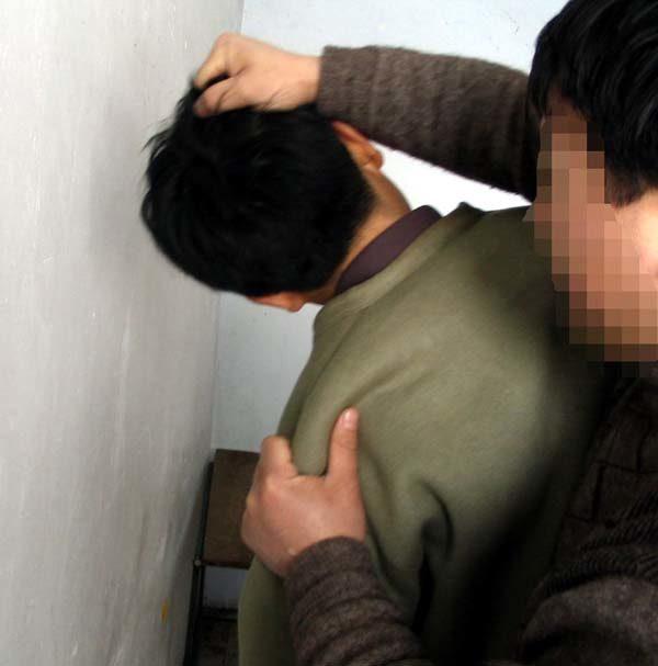 酷刑演示:揪頭髮撞牆。(明慧網)
