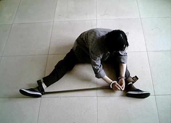 酷刑演示:戴鐵支棍。(明慧網)