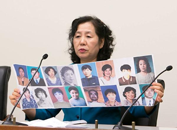 從大連抵美的法輪功學員王春彥展示了她熟識的被迫害致死的法輪功學員的照片。(明慧網)