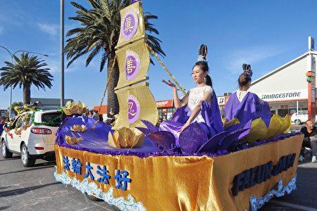 法船上兩位仙女端坐在金色和紫色的蓮花中打坐,展示法輪功功法。(章正/大紀元)