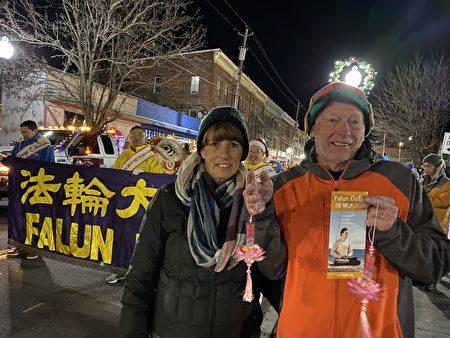"""参加游行的Ed老夫妇表示他们家人都喜欢印有中英文""""法轮大法好""""的莲花吊坠。"""