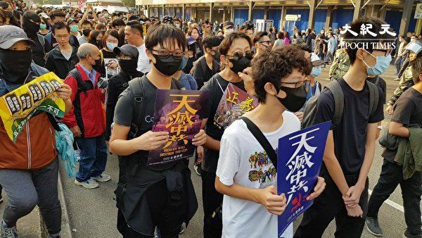 圖為2019年12月1日,港人發起尖沙咀遊行,民眾手拿各種「天滅中共」標語。 (駱亞)