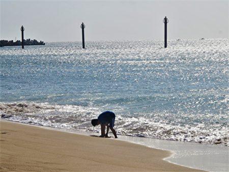 在晴朗的日子,金色的陽光把山水沙灘的海水照映得閃閃發光。