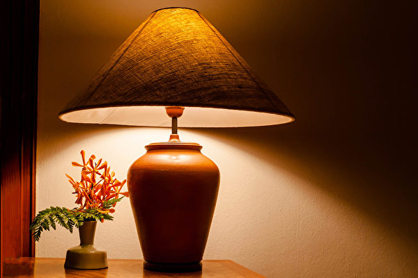 Vintage table lamp light on wooden table with flowers .Fotolia