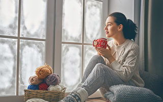 Beautiful young woman sitting by the window and looking at frozen glass. Girl enjoying warm beverage. Fotolia