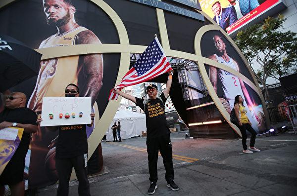 圖為10月22日美國洛杉磯斯台普斯中心外,支持香港抗議活動的民眾舉著美國國旗,抗議美國職業籃球賽NBA向中共叩頭。(Mario Tama/Getty Images)