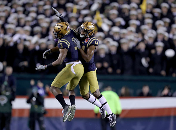PHILADELPHIA, PENNSYLVANIA - DECEMBER 14: Micah Farrar #14 and Cameron Kinley #3 of the Navy Midshipmen celebrates after Navy Midshipmen recovered the ball in the fourth quarter against the Army Black Knights at Lincoln Financial Field on December 14, 2019 in Philadelphia, Pennsylvania.The Navy Midshipmen defeated the Army Black Knights 31-7. (Photo by Elsa/Getty Images)