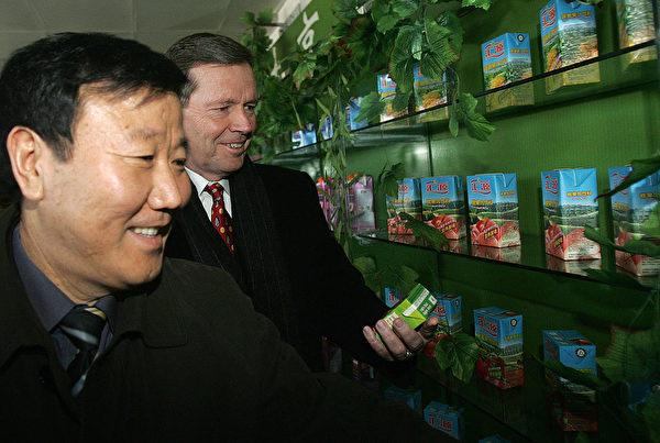 2007年匯源果汁的最輝煌時期,美國時任衛生部長萊維特(Mike Leavitt,右)曾參觀匯源果汁集團,左為朱新禮。( PETER PARKS/AFP via Getty Images)