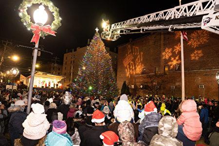 高高的重型吊车载着圣诞老人,在夜空中缓缓移向圣诞树,人们翘首以盼圣诞点灯时刻的到来。