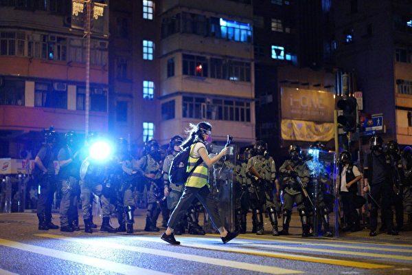 新唐人電視台記者柯婷婷在香港前線進行直播,旁邊是防暴警察。(李明真/大紀元)