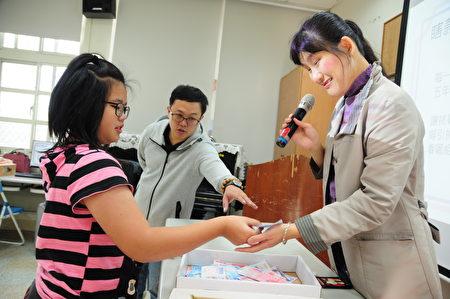 小朋友和老師互動,學習視障者如何辨識千元大鈔