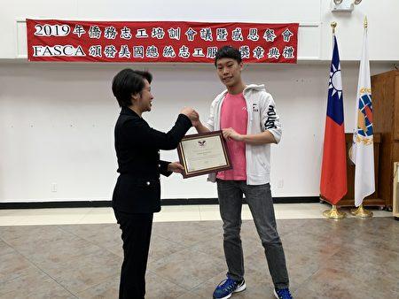 经文处处长颁奖给总统志工服务金奖的李钧彦。
