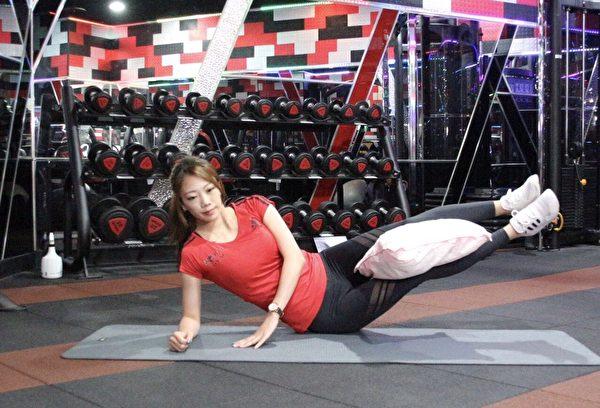 边看电视边瘦身的懒人运动之四:大腿夹枕头侧躺抬腿。(World Gym提供)