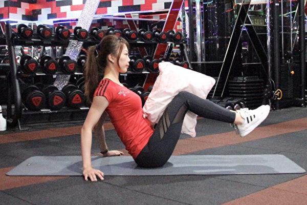 边看电视边瘦身的懒人运动之一:卷腹大腿夹枕头。(World Gym提供)