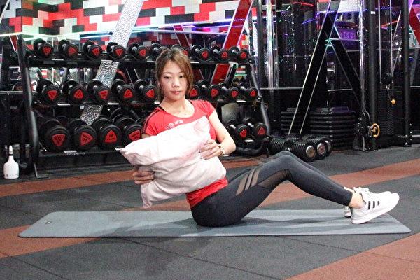 边看电视边瘦身的懒人运动之二:枕头俄罗斯转体。(World Gym提供)