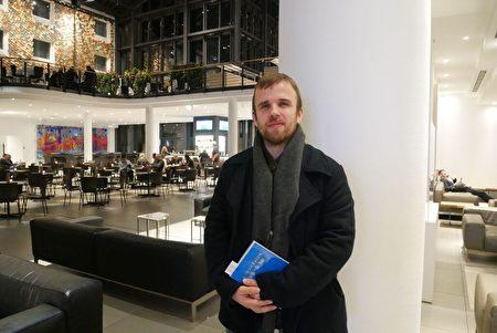 2019年12月29日,一年一度德國法輪大法修煉心得交流會在柏林召開。來自不來梅的西里爾(Cyrill)傾聽會上發言後,講述自己的體會。他手上拿著德文版的《轉法輪》。(穆華/大紀元)