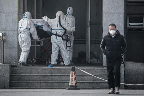 1月18日,武漢一所醫院的醫護人員抬著一名神秘肺炎患者。(STR/AFP)