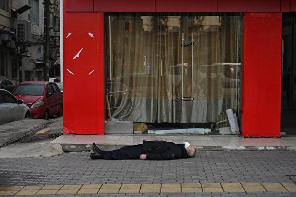 2020年1月30日,一名戴著口罩的老人倒斃在武漢一家醫院附近的一條街的人行道上。(Hector RETAMAL/AFP)