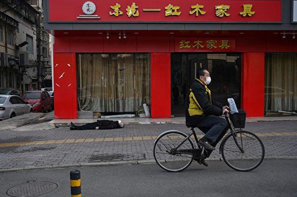 2020年1月30日,一名戴著口罩老人倒斃在武漢一家醫院附近的一條街的人行道上。(Hector RETAMAL/AFP)